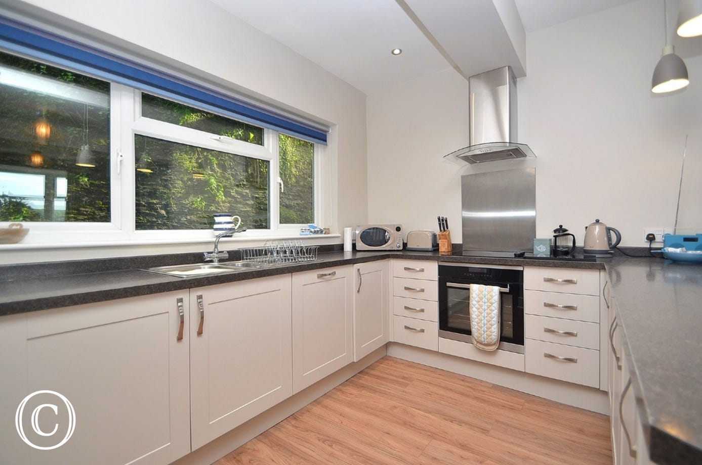 Kitchen: Spacious open plan kitchen with range of high-gloss wall and base units, integrated fridge/freezer, dishwasher, electric oven and hob with extractor hood. Utility with washing machine and dryer.