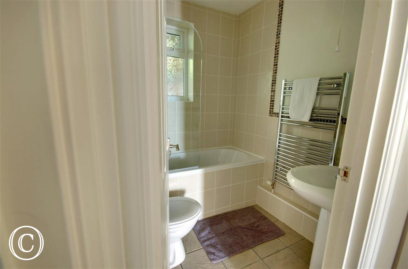 The pristine modern bathroom has bath, shower over bath, WC and basin