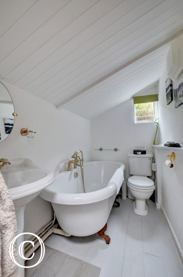 The bathroom with roll top bath and sloped ceiling