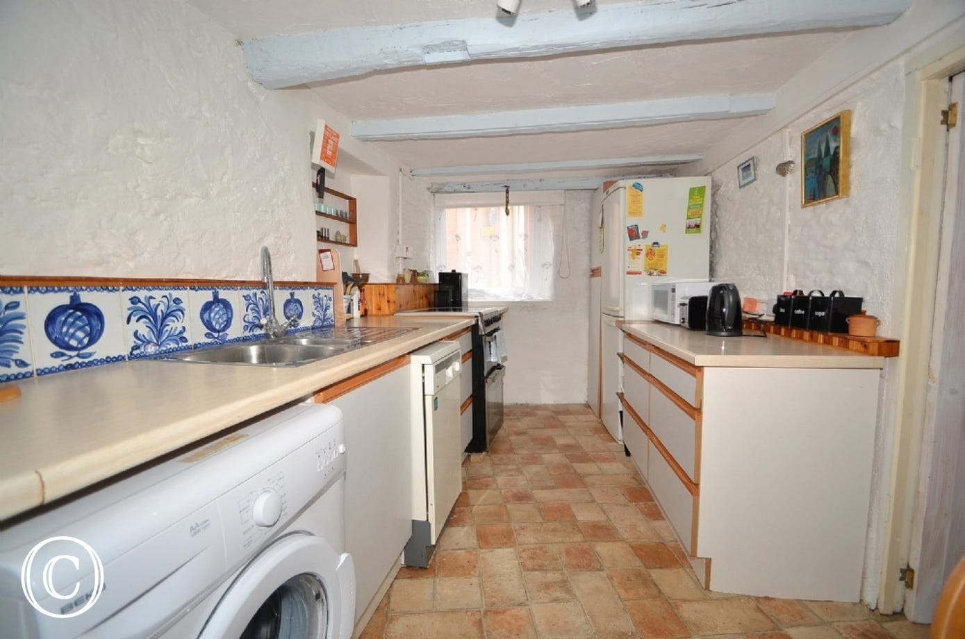 Kitchen: Galley, cottage style with quarry tiles floor. Washing machine, dishwasher, free standing electric cooker, fridge freezer, microwave, toaster and kettle.