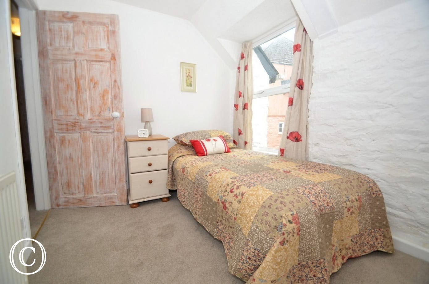Bedroom 3: Single bed with slide out single bed underneath, wall mounted mirror, chest of drawers with a lamp.