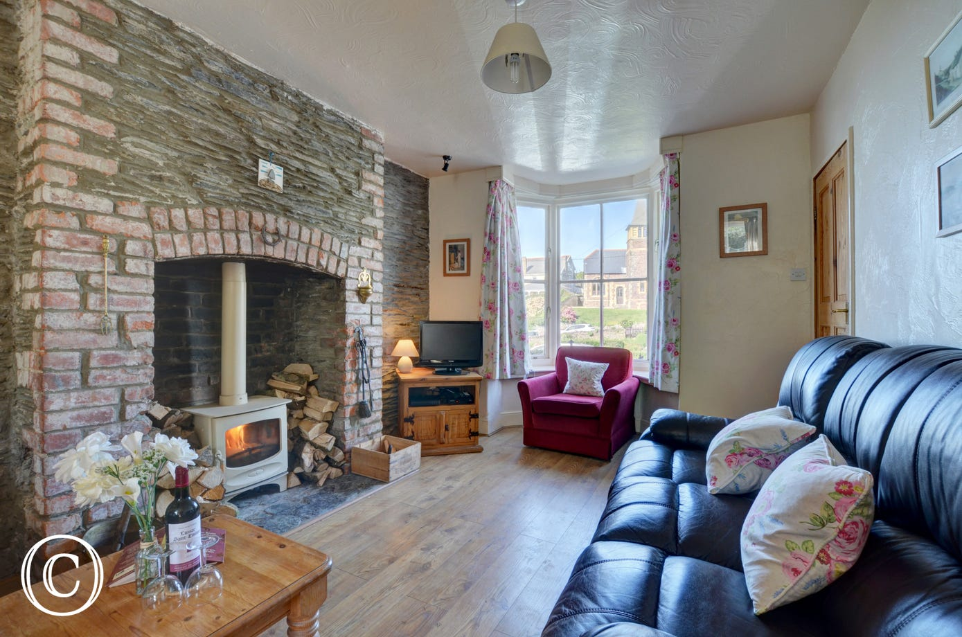 The spacious living/dining room has laminate flooring and a wood burning stove