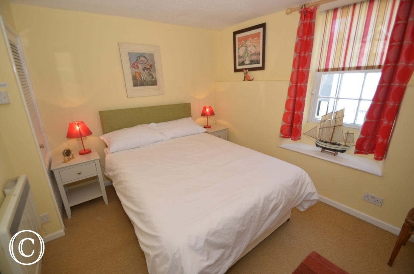 Bedroom 1: At the front of the property, double divan bed with bedside cabinets, side lights, built-in wardrobe and chair.
