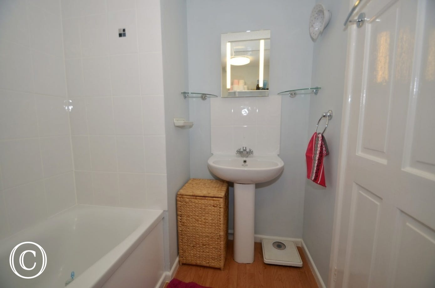 Bathroom: White suite comprising of a panelled bath with electric shower over, low level WC. and a pedestal washbasin with illuminated mirror over.