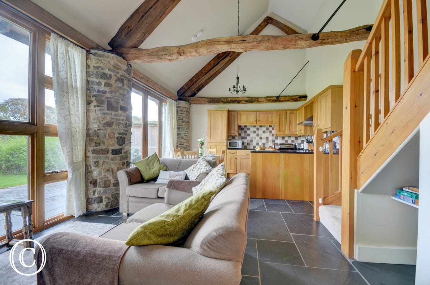 An expanse of glass windows and doors brings the outside in, and the open plan living area features exposed stonework and vaulted oak beams