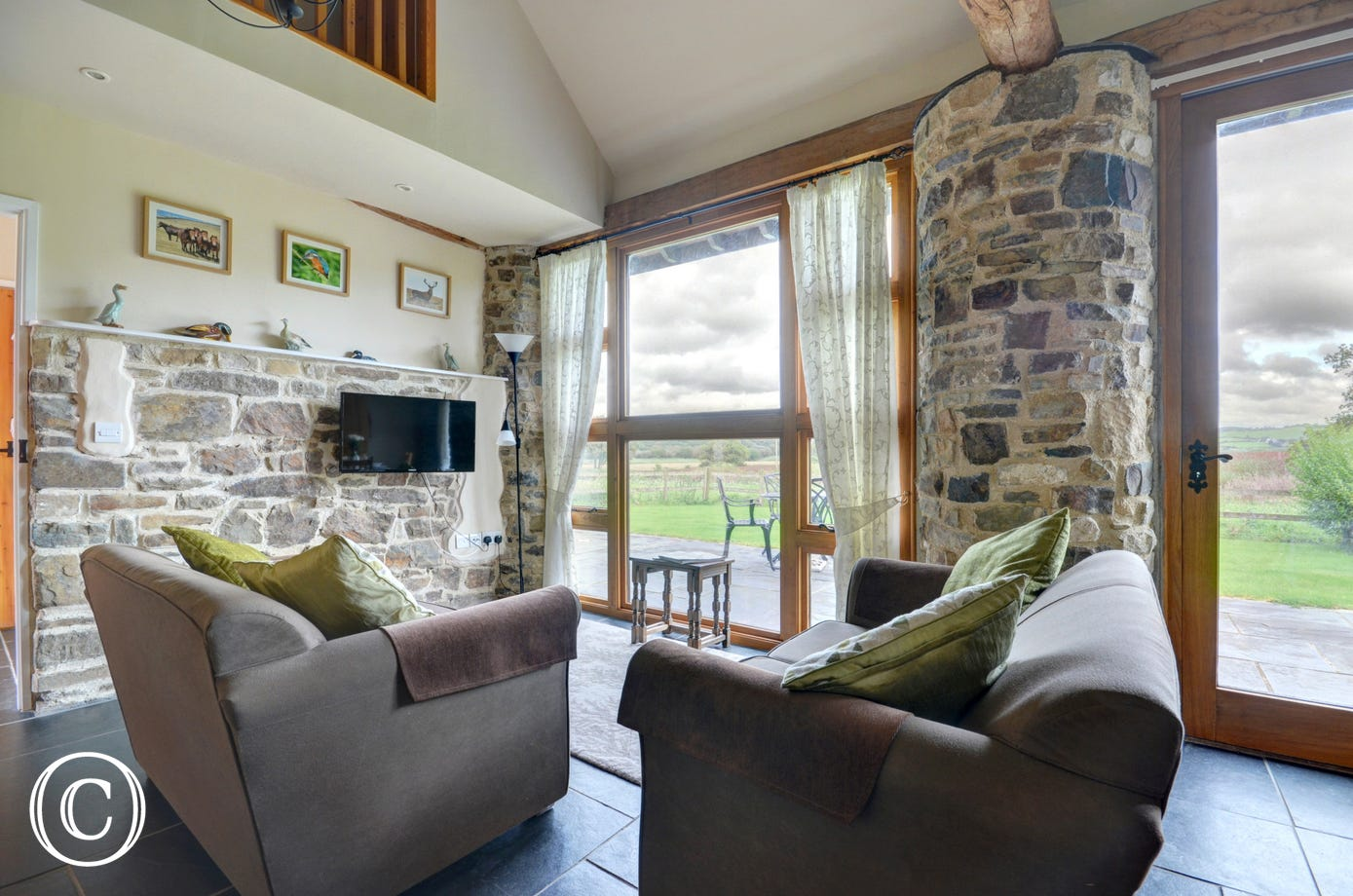 The contemporary furnishings are complemented by slate flooring and a cosy corner with comfy sofas has far reaching views