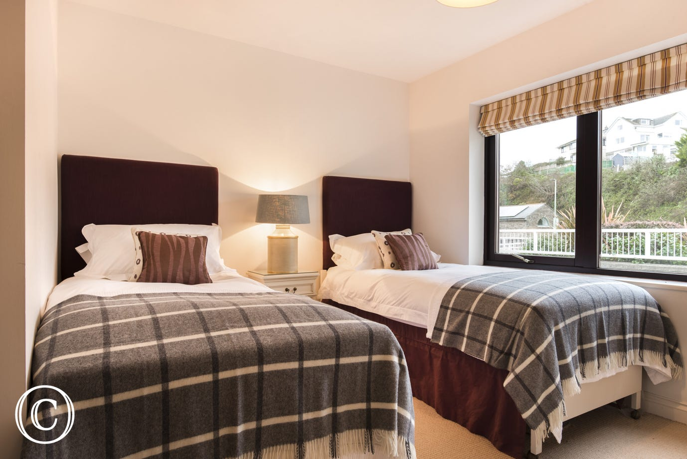 stylish bright twin bedroom with large picture windows in 22 The Moorings Apartment in Kingsbridge