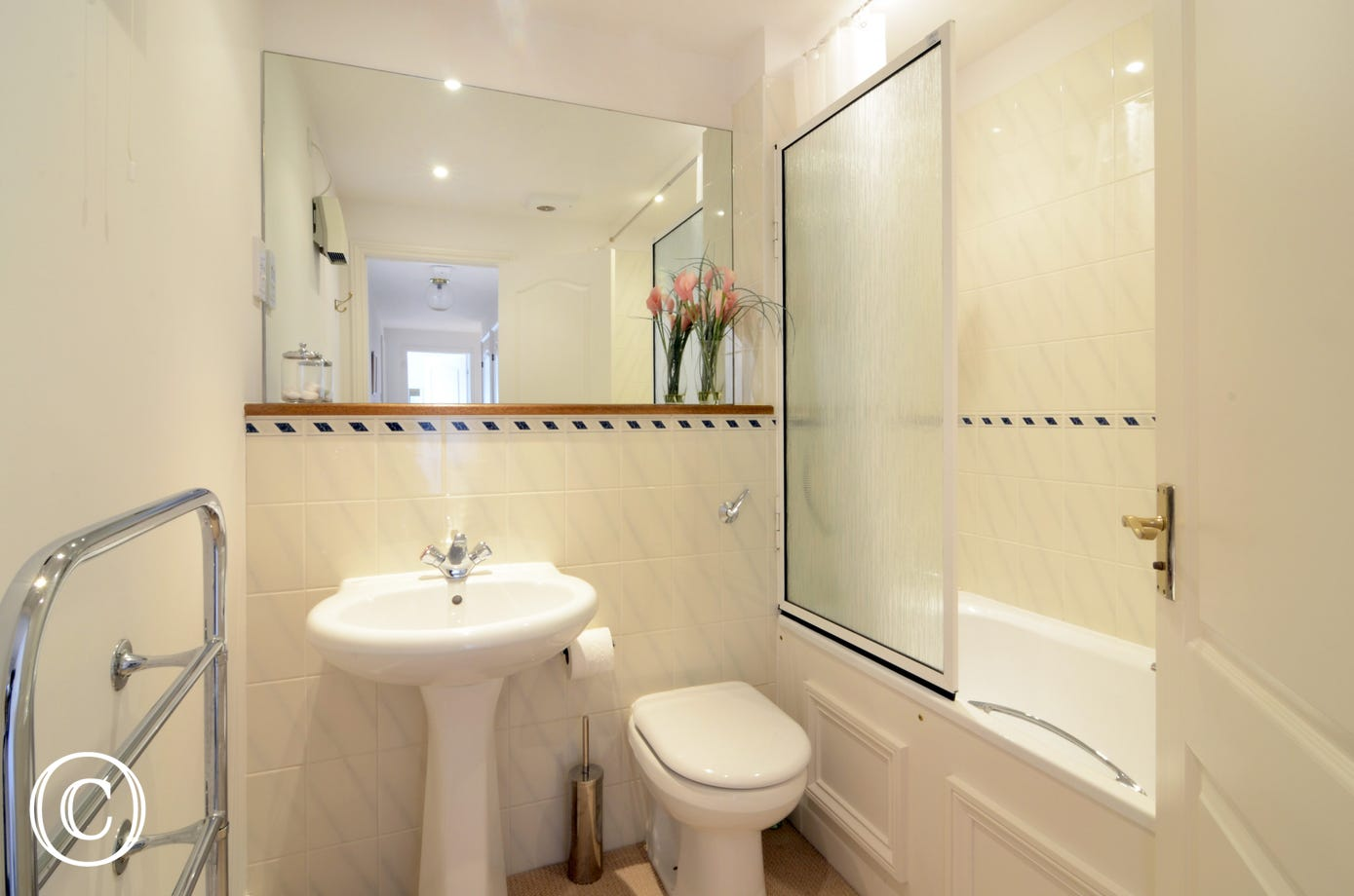 Family bathroom with bath tub, shower over bath, wash basin and toilet, as well as heated towel rail