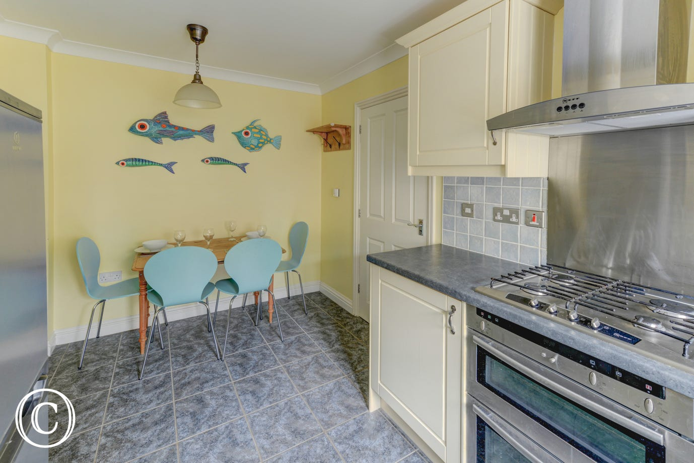 The modern cottage style kitchen/breakfast room has cream units, granite style work surfaces and tiled floor