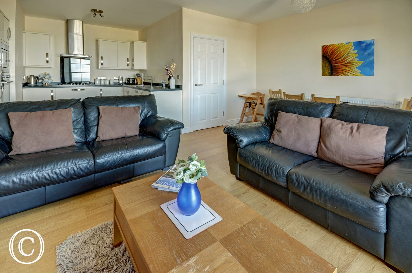 Comfy leather sofas complement the oak style flooring in the sitting area
