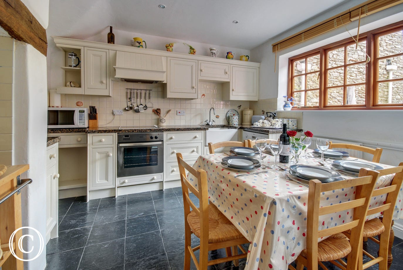 Tiled slate flooring and granite work surfaces create a modern cottage style in the pretty kitchen/breakfast room