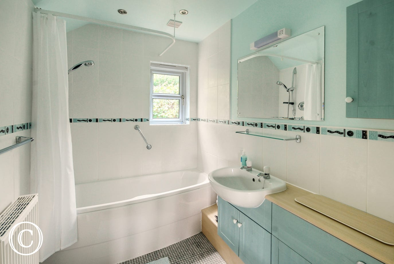 Spacious ensuite bathroom with shower over bath