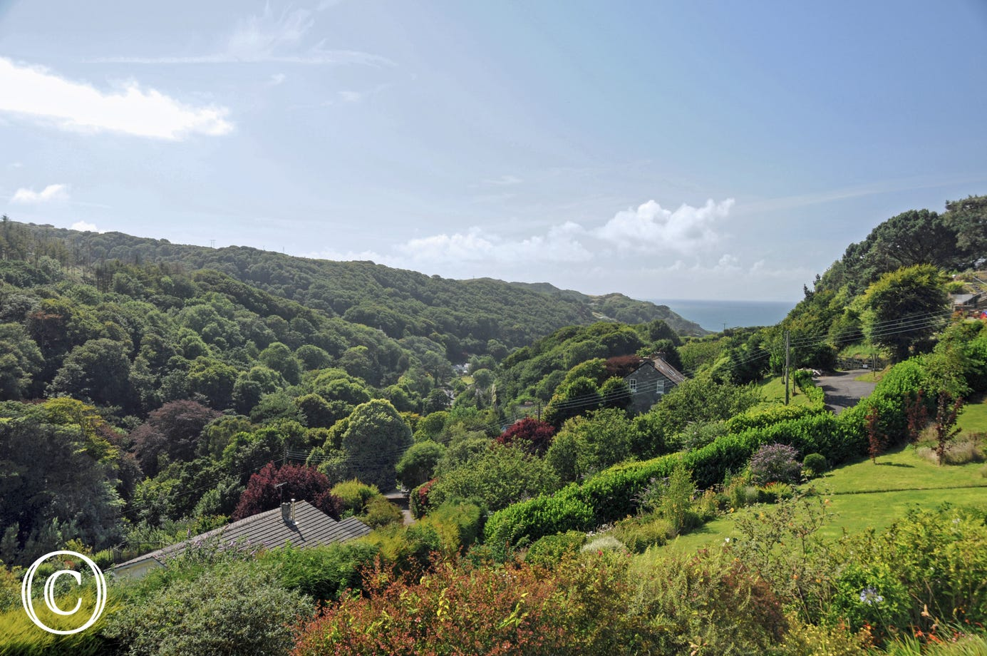 Stunning views across the lush green wooded valley and distant sea views