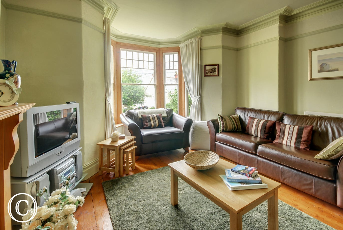 One of the sitting rooms with TV, leather sofas and fireplace