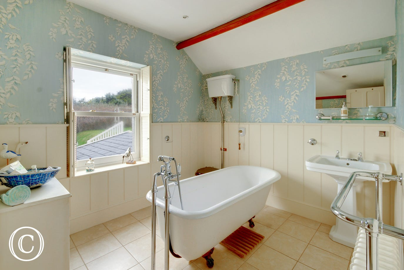 Stylish separate family bathroom with large walk in shower area and freestanding roll top bath