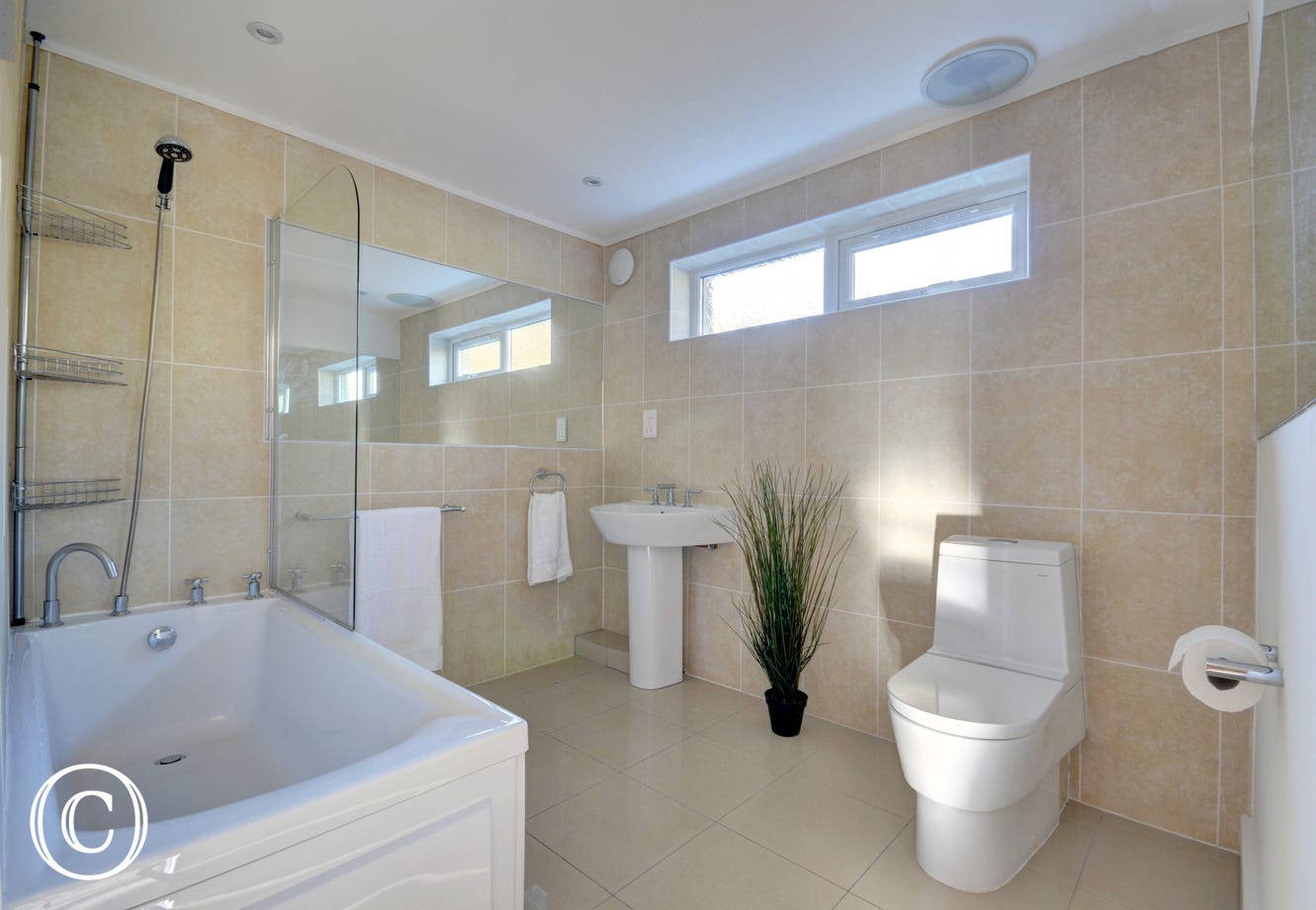 Neutrally decorated family bathroom with shower over bath