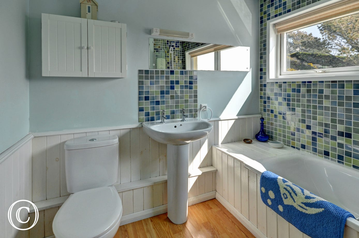 Family bathroom with electric shower over bath, WC and hand basin