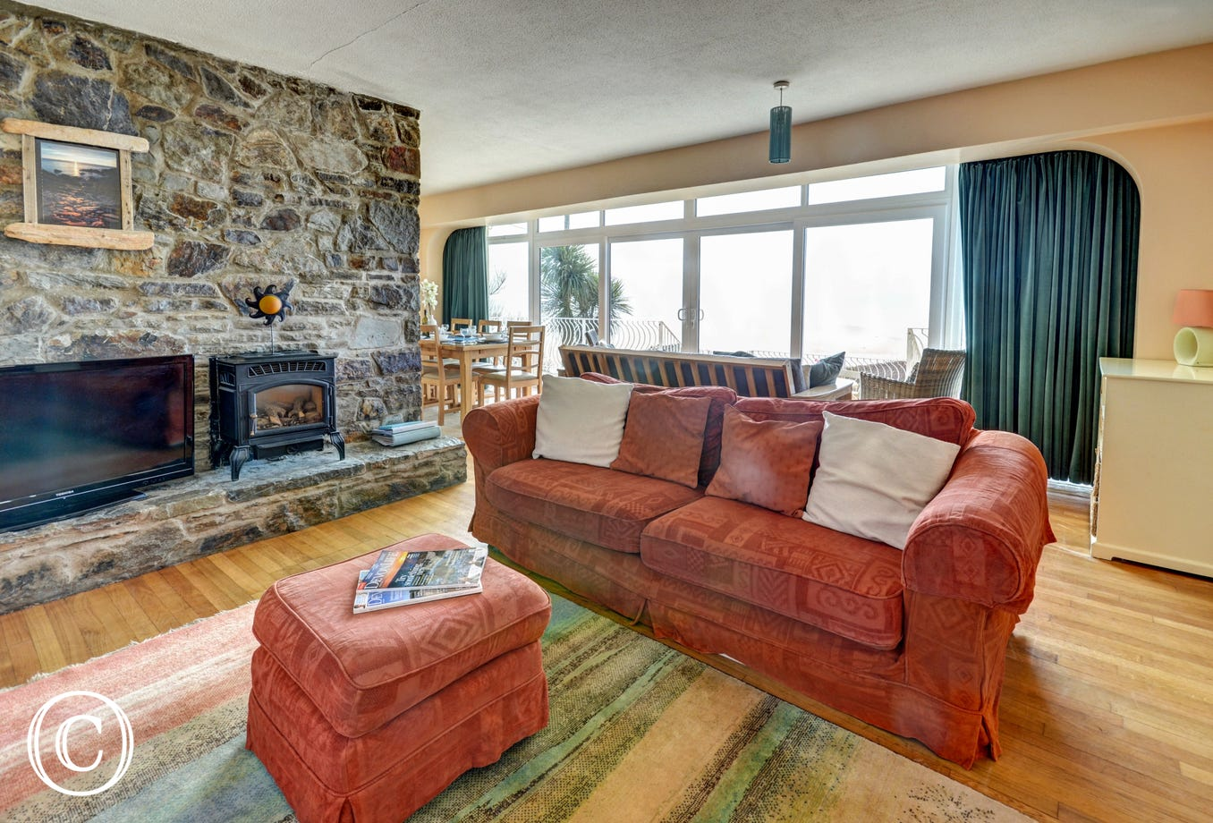 The cosy sitting area has a large TV and stone fireplace with woodburner effect heater