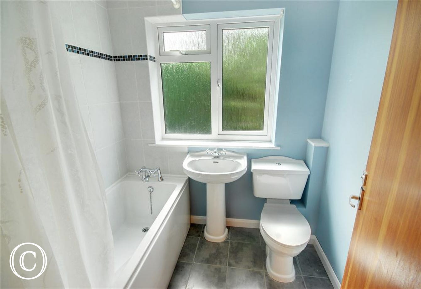 Newly fitted bathroom with a shower over the bath