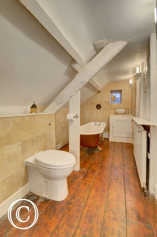 The 2nd floor bathroom is full of character with roll top bath