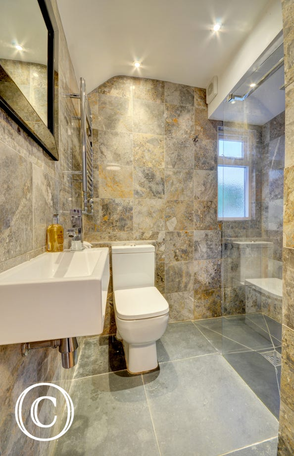 Separate handy wet room with slate floor and Italian marble wall tiles