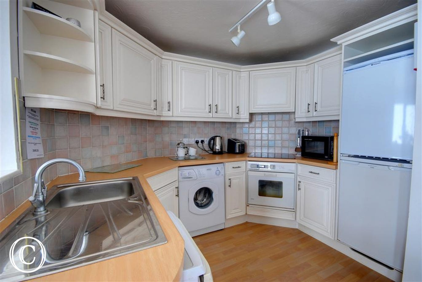 The kitchen is modern and spacious with a large fridge freezer.
