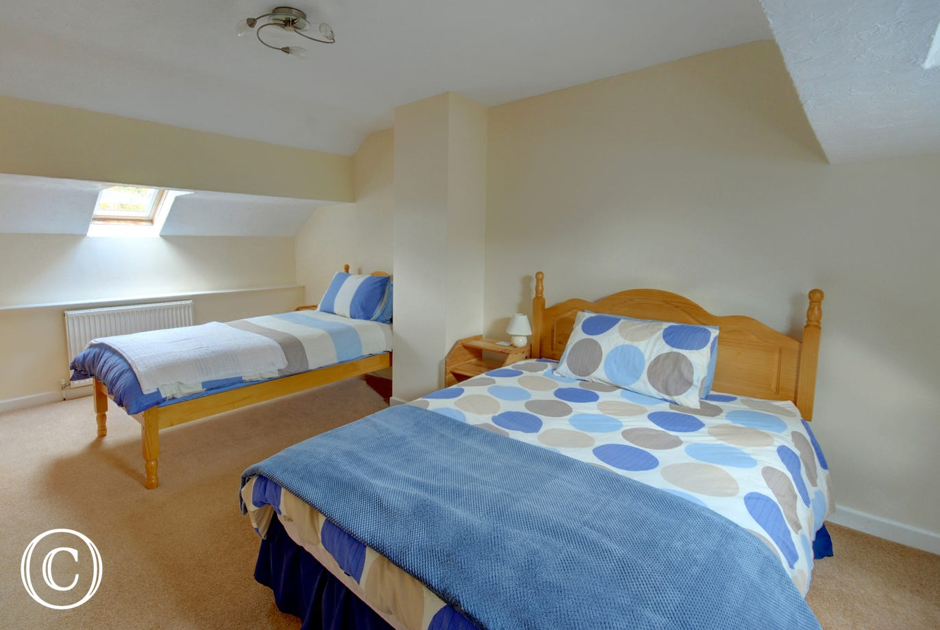 The stylish second bedroom comfortably takes both a double bed and a single bed, a wonderful bonus for flexible sleeping arrangements