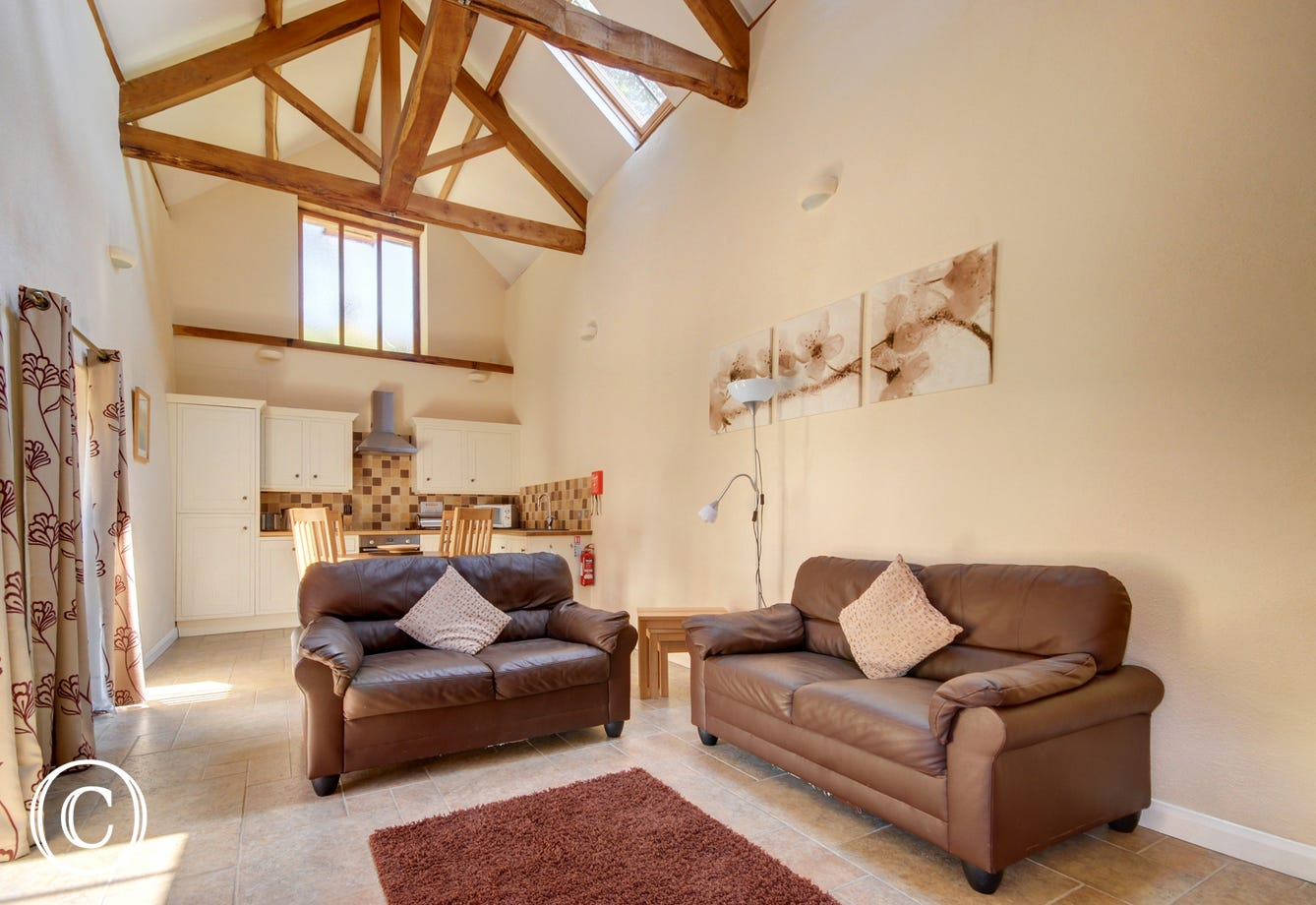 The impressive light and bright open plan living room with high vaulted oak beamed ceiling, comfy leather sofas and country cream kitchen has a contemporary feel