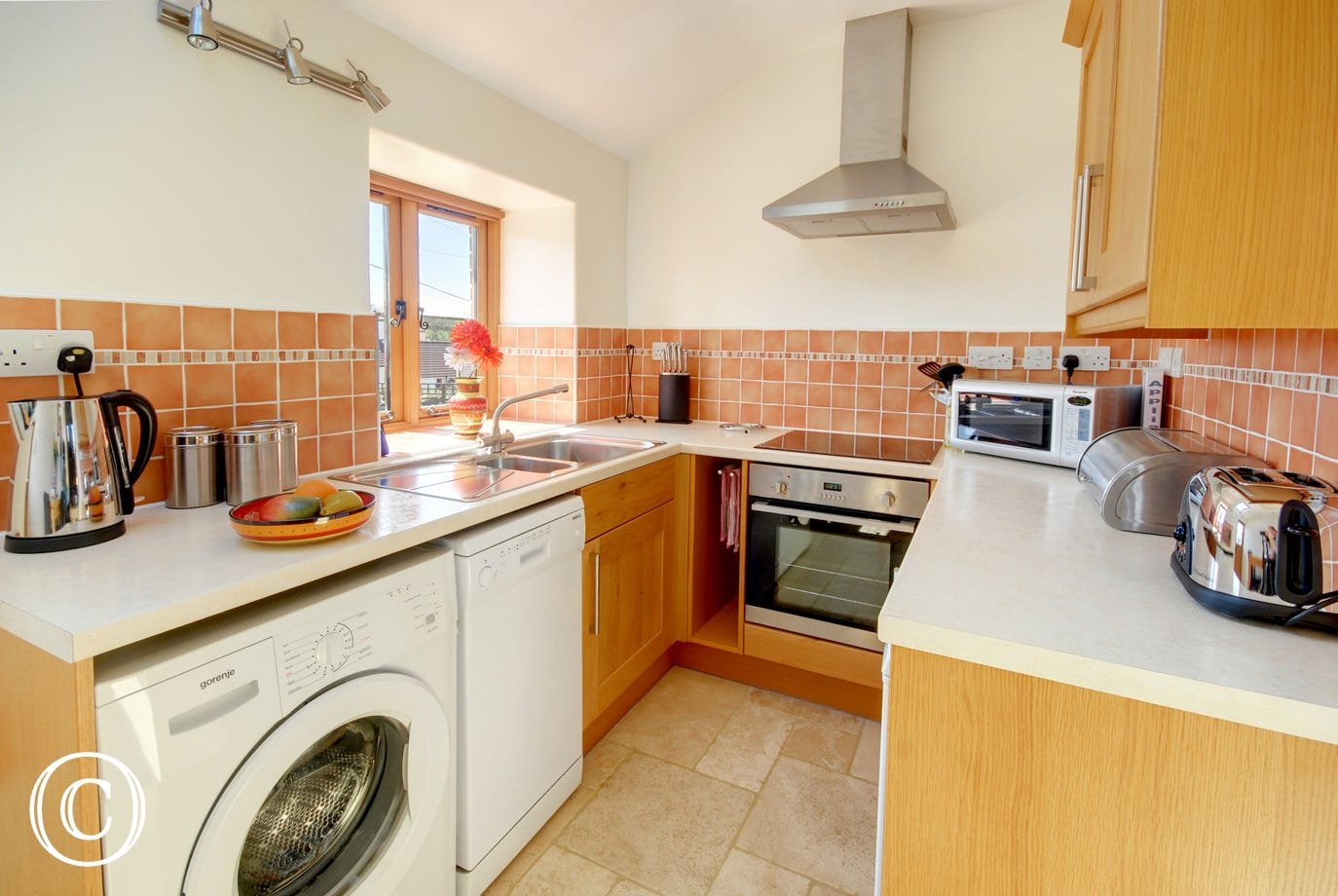 Kitchen with electric oven and hob, microwave, fridge, dishwasher and washing machine