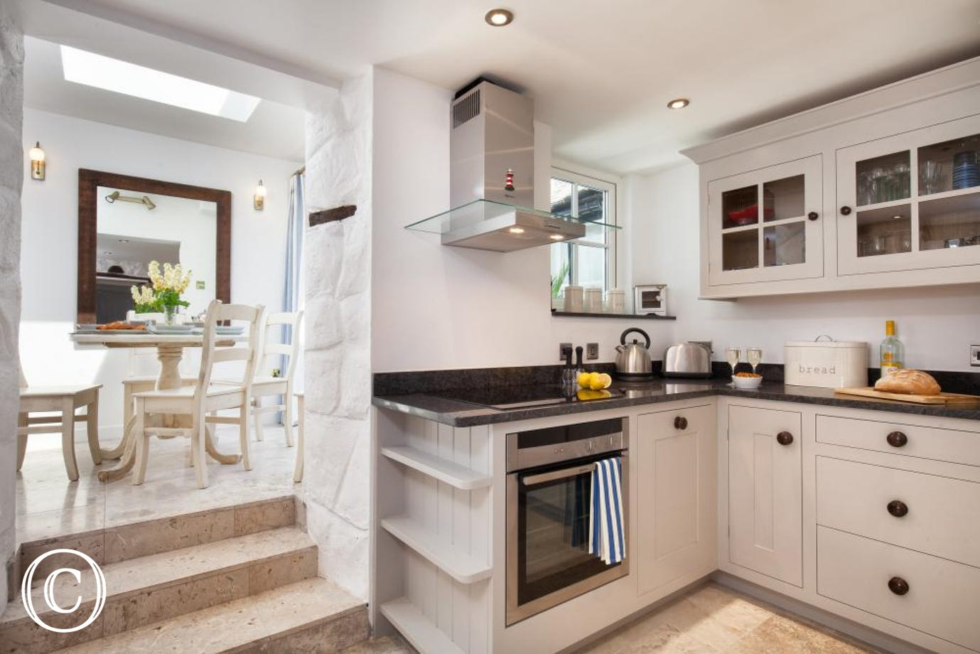 Spacious cottage kitchen with 3 steps to the elegant breakfast room.
