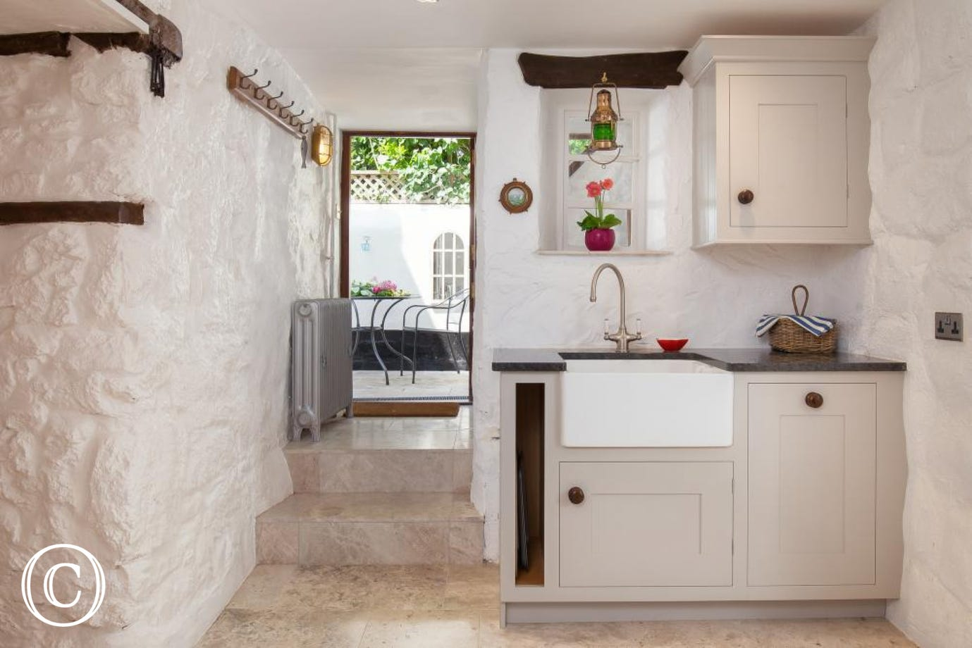 Large ceramic sink & dishwasher with a small utility area next to the back stable door.
