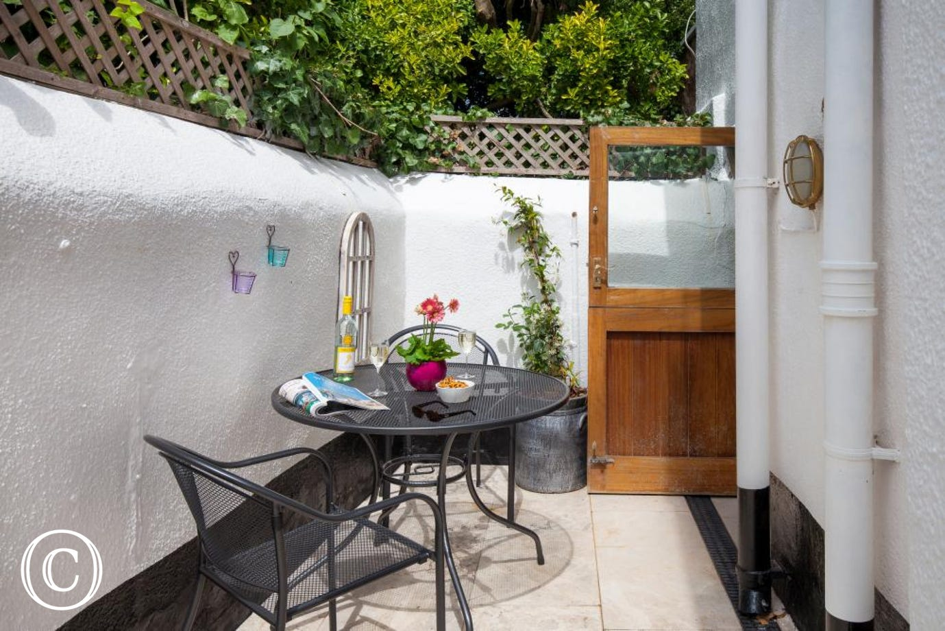 Sunny outside enclosed courtyard with table and chairs.