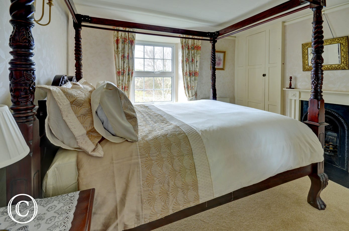 Wooden four poster bed in the master bedroom
