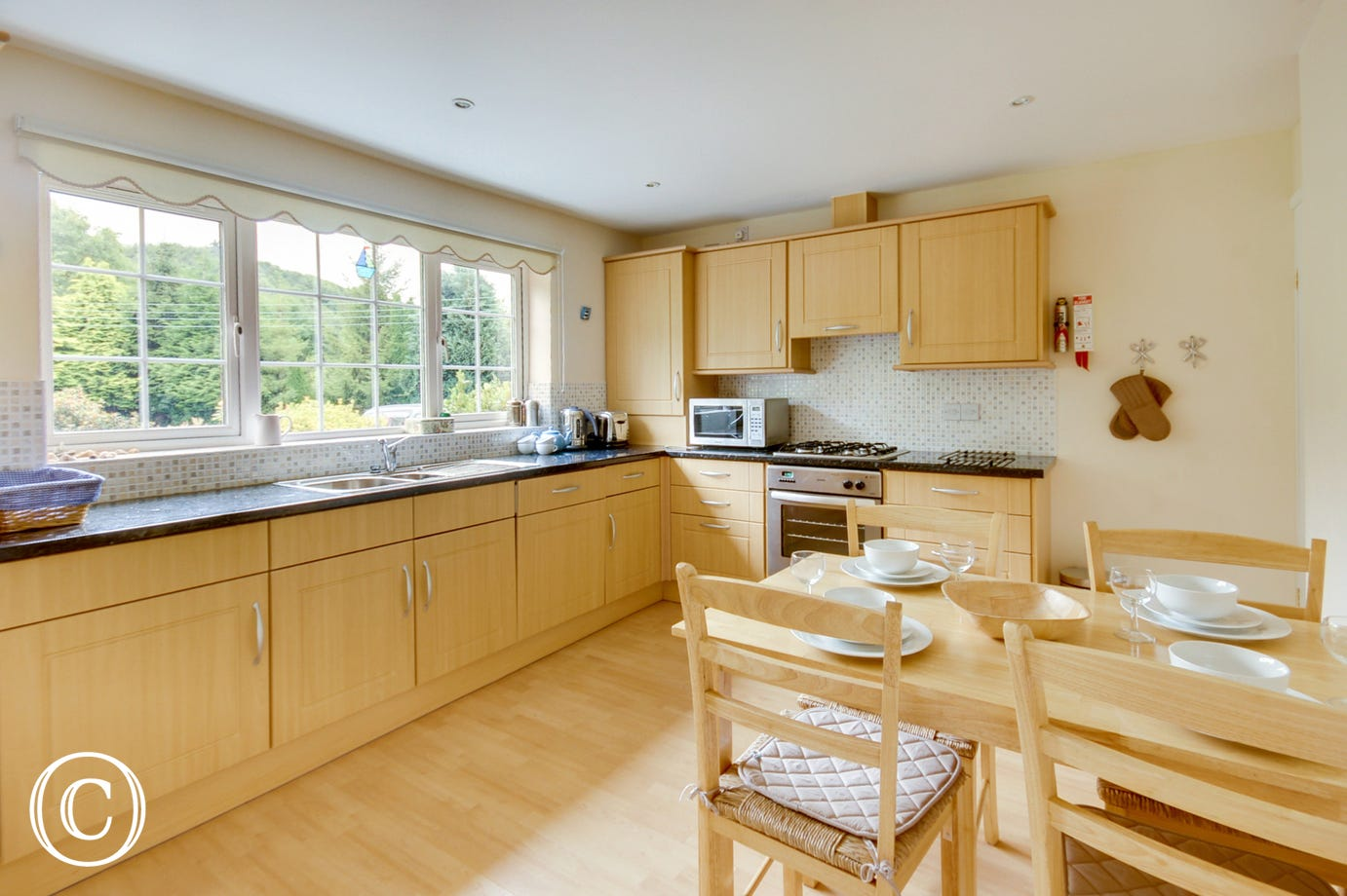 The spacious dining kitchen boasts modern beech units complemented by granite style worktops