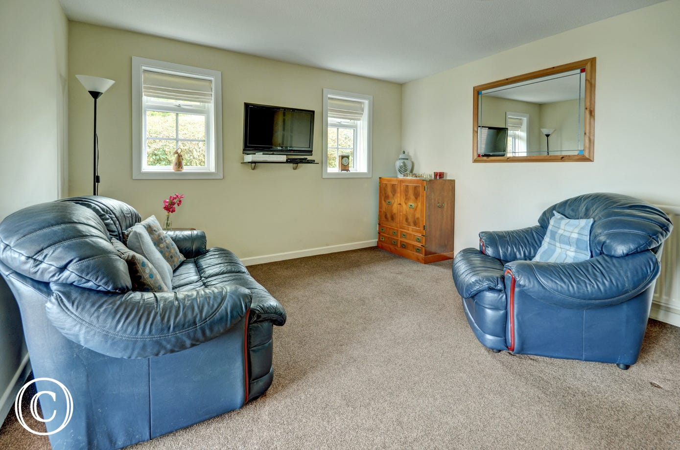 Comfortable leather sofas in the sitting room and wall mounted TV