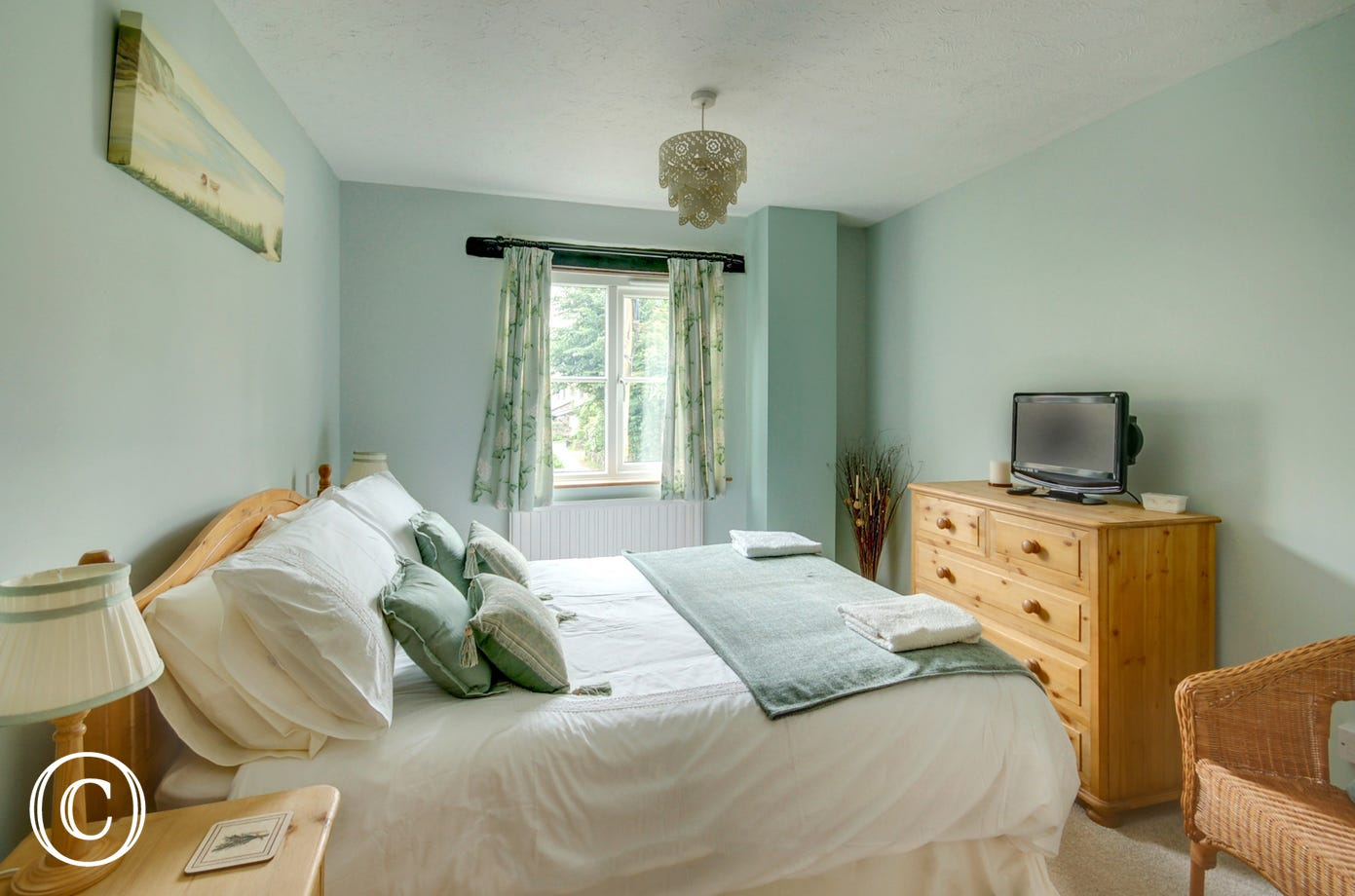 The pretty master bedroom with double bed, ensuite bathroom and TV