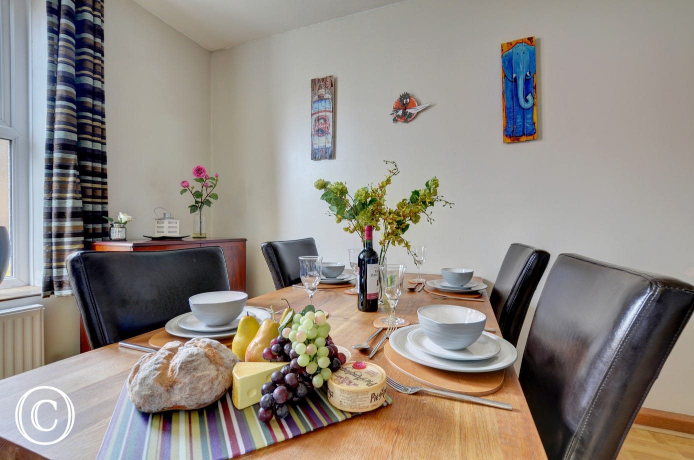 The separate dining room has a large dining table and comfortable leather dining chairs