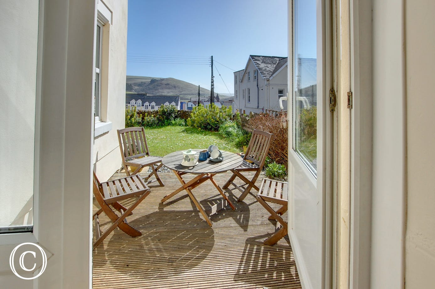 French doors provide access onto a small decked patio and garden which overlooks the village and beach