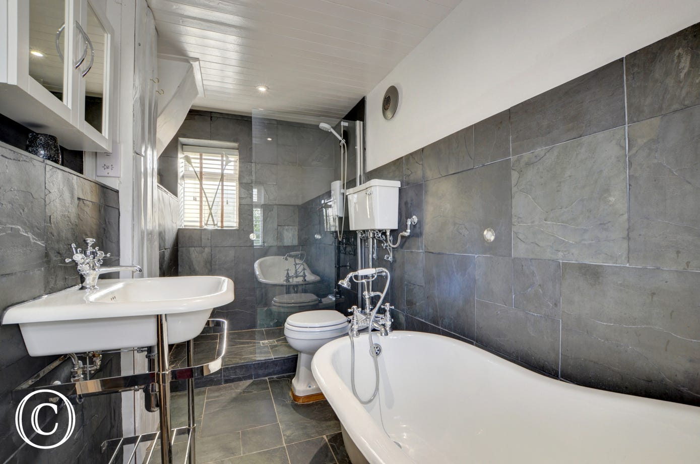 The tasteful ground floor family bathroom has a slipper bath, walk-in shower, WC and basin as well as under floor heating