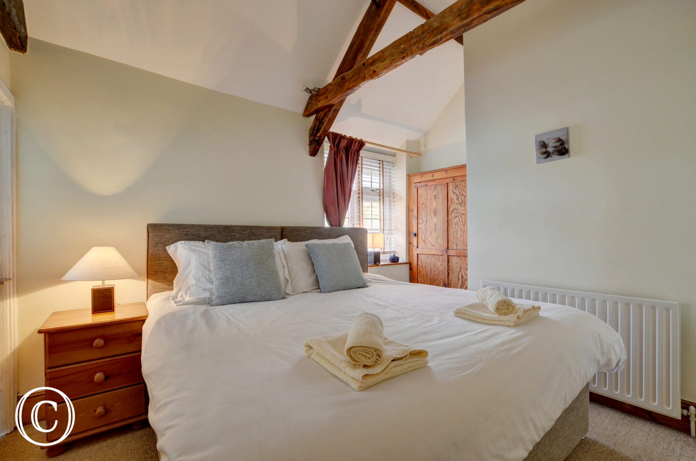The master bedroom with super king bed and original beams, exposed stonework and pine furniture