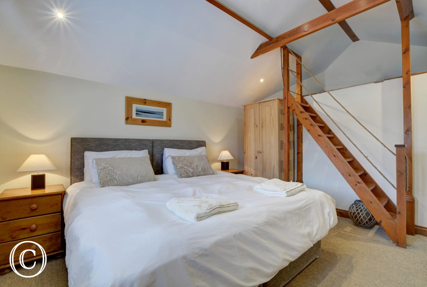 Stairs within the bedroom provide access to an open storage area with travel cot and child's buggy available for visitors use