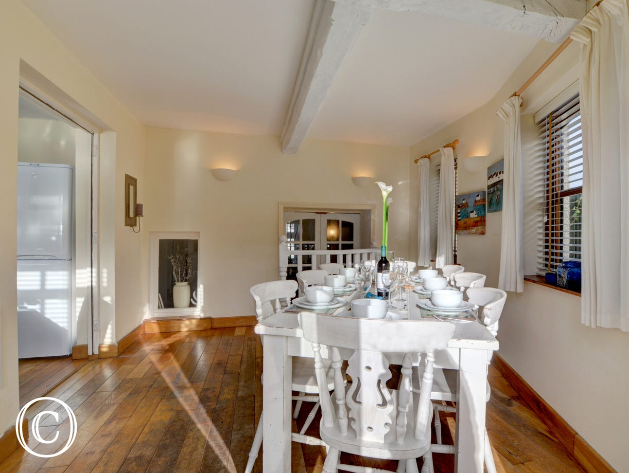 Opening off the kitchen is the dining area with comfortable seating for 8