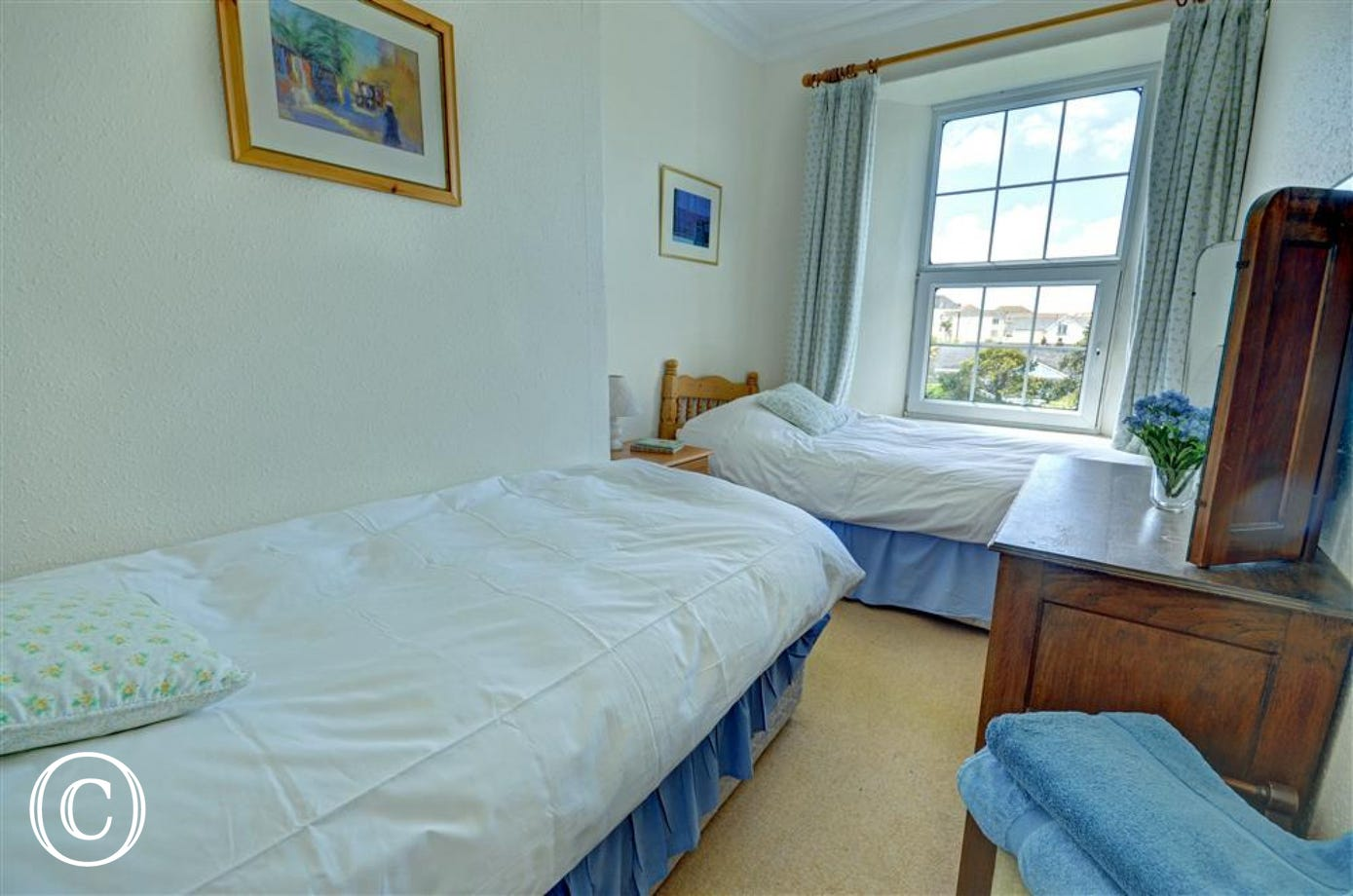 A twin bedded room that has been traditionally furnished