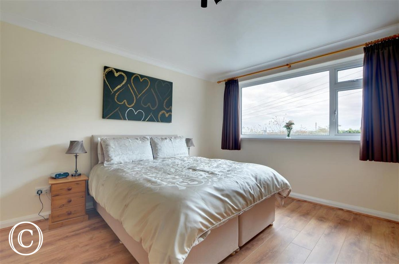Spacious master bedroom with Smart TV and ensuite shower room with level access shower unit, WC and basin