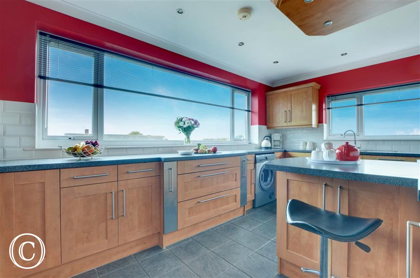 Huge picture windows capture the views from every angle in the stylish kitchen