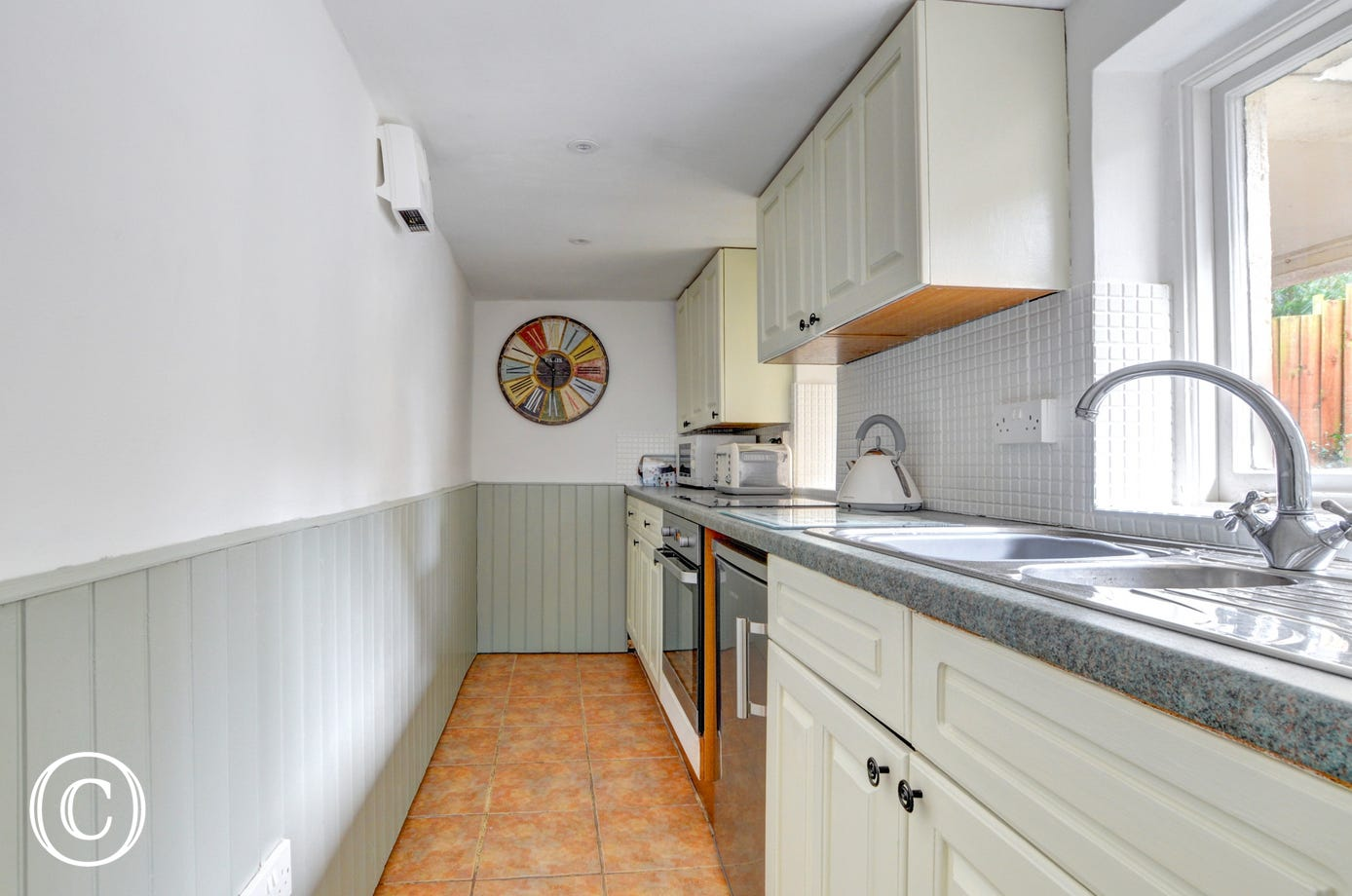 A small fitted galley kitchen is well equipped and has views up over the garden