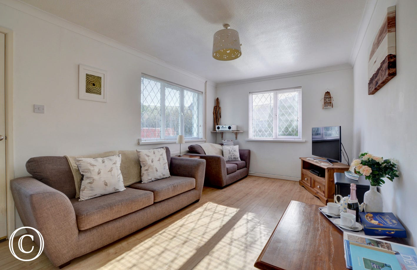 Plenty of comfortable seating in the sitting room, large TV and electric woodburner effect fire