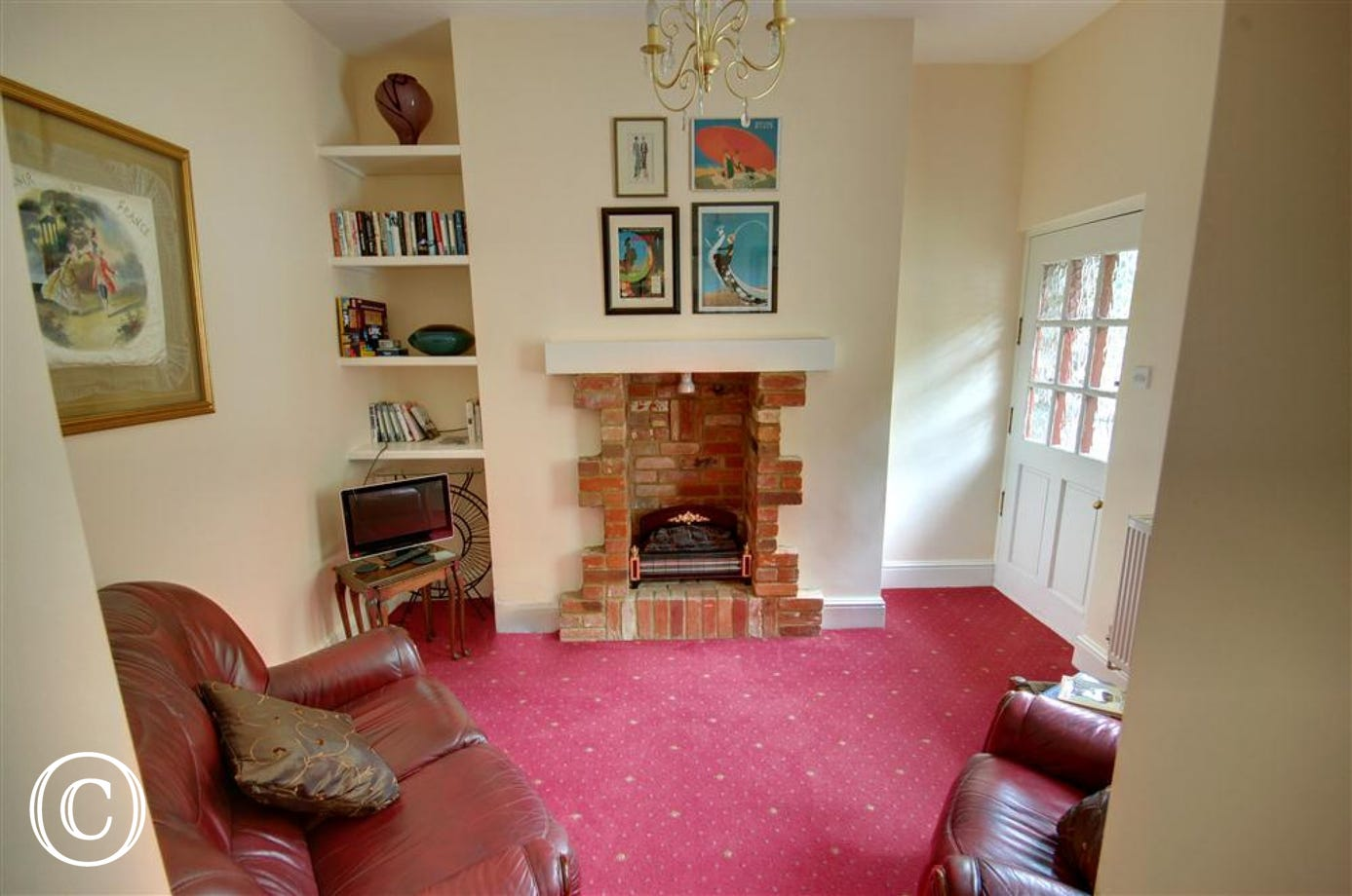 Small sitting room with electric fire in feature fireplace