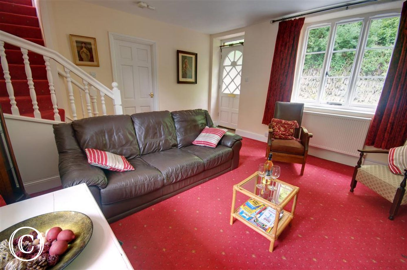 Sitting room with comfortable leather sofa and entrance to the property
