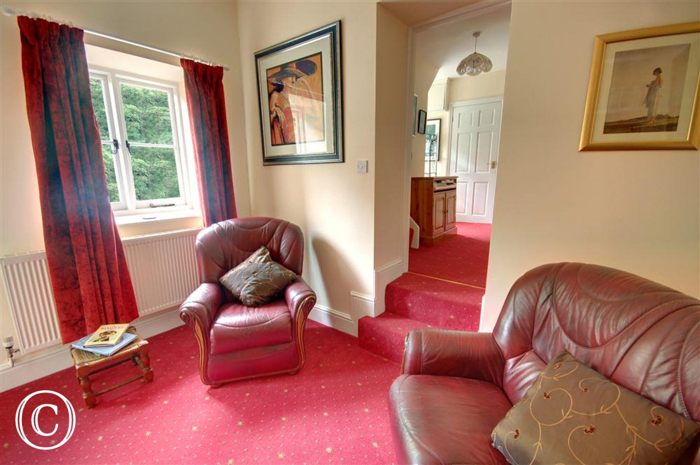 Two comfortable chairs in the lower sitting room with stairs to the shower room